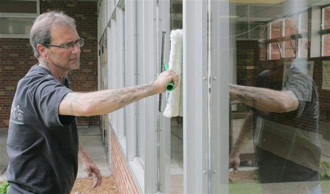 Steve Domurat, a 23-year veteran of cleaning and maintaining Wauwatosa Public Schools, will be part of the district's plan to layoff half of the custodial staff and hire contractors to clean the schools. Domurat is cleaning windows outside of Underwood Elementary School where he is currently assigned.