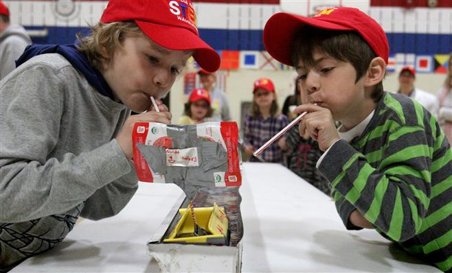 Ryan Westpahl (left) and David Miller propel their team's sailboat along the race trough as one of the activities during the Wauwatosa STEM School's Recycling Regatta on May 16. Teams created sailboat to race using material recycled from other products.