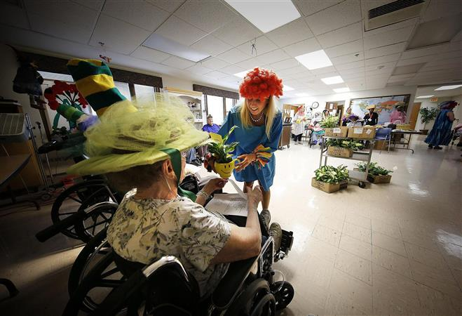 Ninety-four-years-young Rose Marie Letizia is presented with a flower by Melissa Maas at the Luther Manor nursing home Thursday, July 21. Every resident was given flowers.