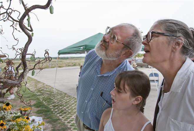 Marlena Green and her grandparents, Bobbie Groth and Don Lawson, look at monarch butterflies in chrysalis form. The living display was part of the Blue Moon Event on Aug. 31.