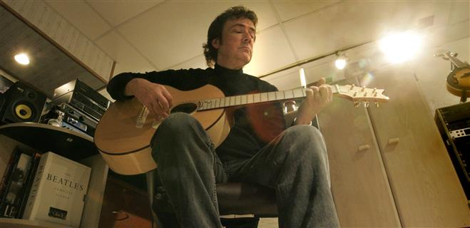 "Mark Lansing strums one of the acoustic guitars from his collection in his home studio where he produced his solo CD ""Solstice""."